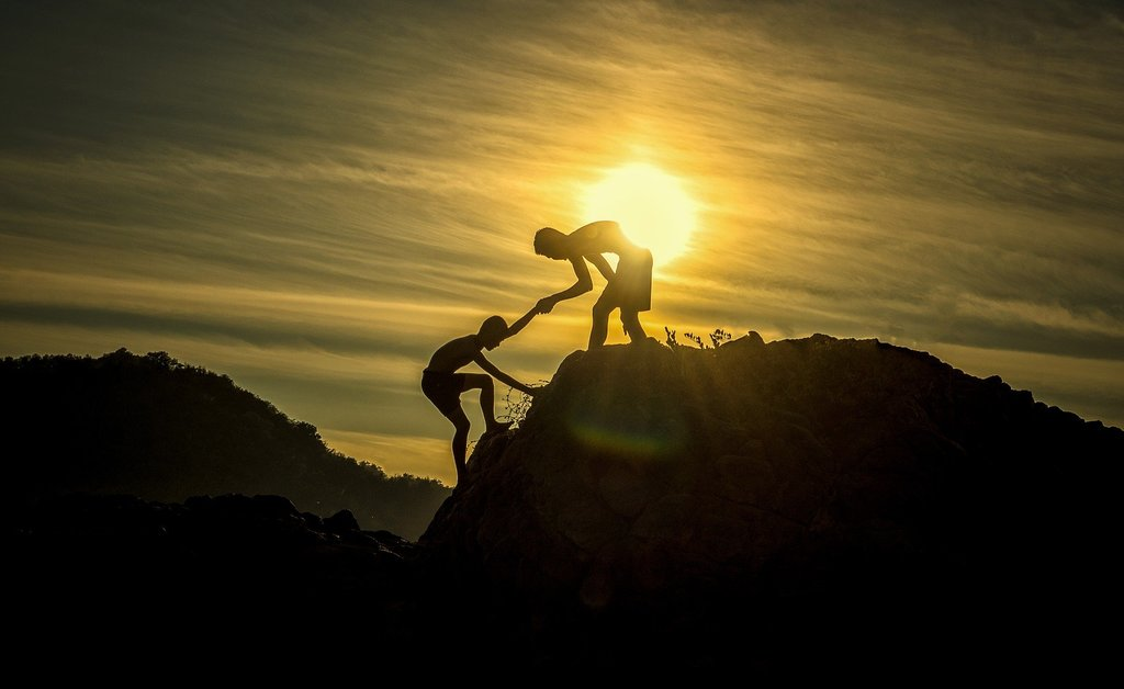 Muž pomáhá druhému nahoru za sluncem