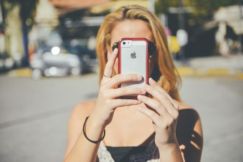 Holka na telefonu řeší Instagram